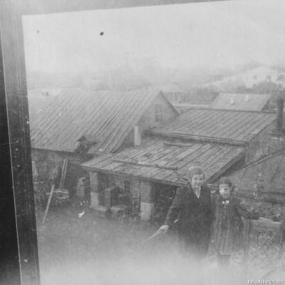 Лиля и Вера Конюшая на лесенке, ведущей на крышу нашего дома. На заднем плане видна бывшая конюшня. В правой части фотографии – крыша женской консультации. 1952 год.