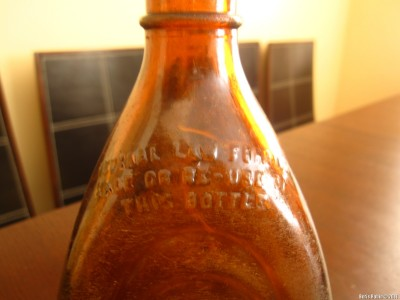 Текст: «Federal Law forbids sale or re-use of this bottle»