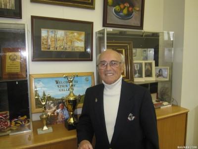 Арнольд Хальфин около своих кубков, наград и картин