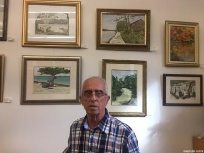 Марк Рабинович на фоне своих картин